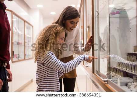 Happy mother and daughter looking at display while shopping in jeweler shop - stock photo