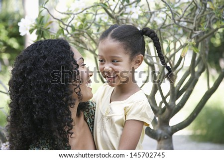 Happy mother and daughter looking at each other in garden - stock photo