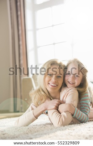 Happy mother and daughter lying on floor at home