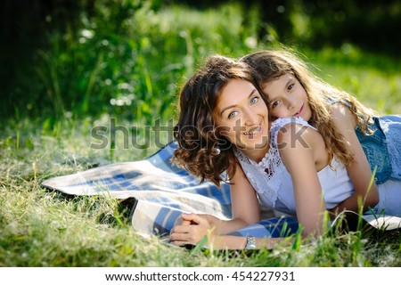 Happy mother and daughter lying outdoors smiling and hugging - stock photo