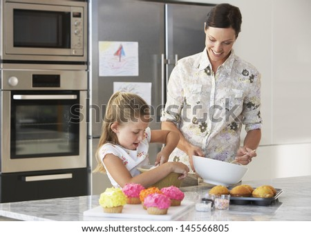 Happy mother and daughter making cupcakes in kitchen - stock photo