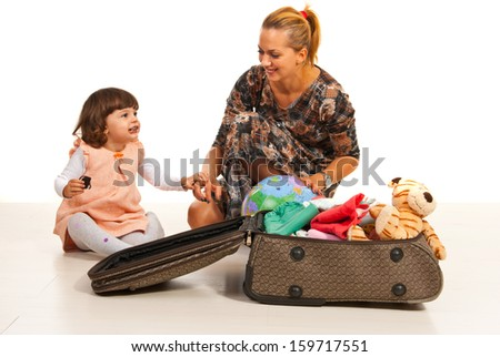 Happy mother and daughter making luggage isolated on white background - stock photo