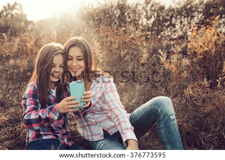 happy mother and daughter making selfie outdoor in summer. Happy family spending summer vacation together outdoor. Cozy warm mood, lifestyle capture. - stock photo