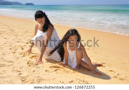 Happy mother and daughter on a seashore - stock photo