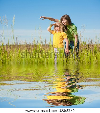 Happy mother and daughter on field. Reflected in Water. - stock photo