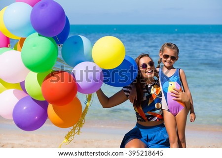 Happy mother and daughter on the beach, holding flying colorful balloons - stock photo