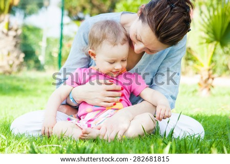 Happy mother and daughter on the grass - stock photo