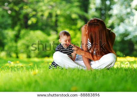 Happy mother and daughter on the green grass - stock photo