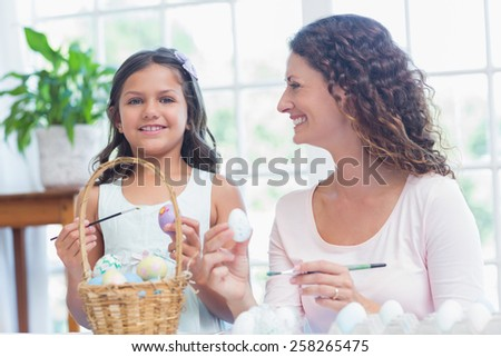 Happy mother and daughter painting easter eggs in the living room - stock photo