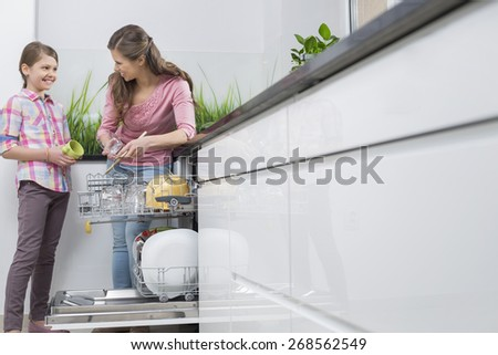 Happy mother and daughter placing glasses in dishwasher at kitchen