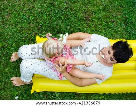 Happy mother and daughter play on the grass - stock photo