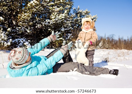 Happy mother and daughter playing in snow - stock photo