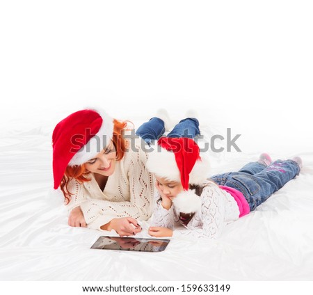 Happy mother and daughter playing with a tablet pc on Christmas morning - stock photo