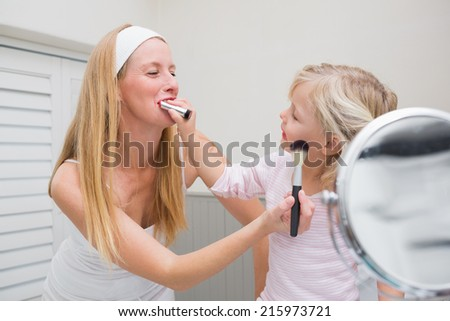 Happy mother and daughter playing with make up at home in the bathroom - stock photo