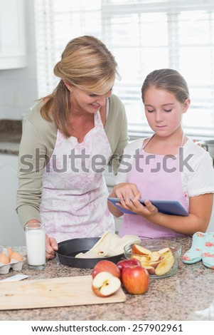 Happy mother and daughter preparing cake together with tablet at home in the kitchen - stock photo