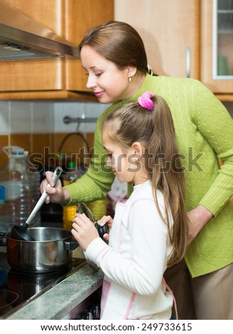 Happy mother and daughter preparing soup together at home kitchen and smiling. Focus on girl