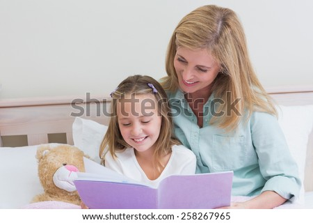 Happy mother and daughter reading a book in bed - stock photo