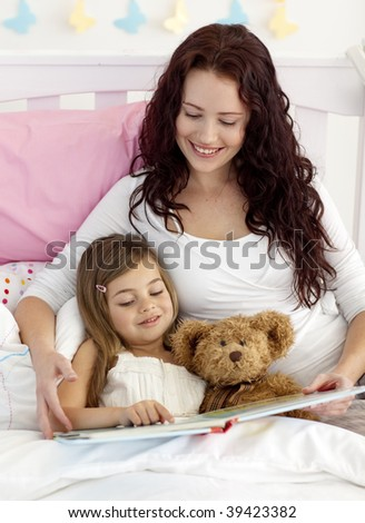 Happy mother and daughter reading a book together in bed