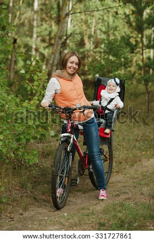 happy mother and daughter riding bike in the forest