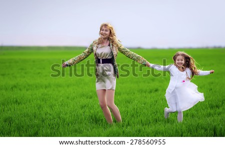 Happy mother and daughter run on the meadow - stock photo