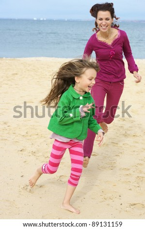 Happy mother and daughter running at beach. - stock photo