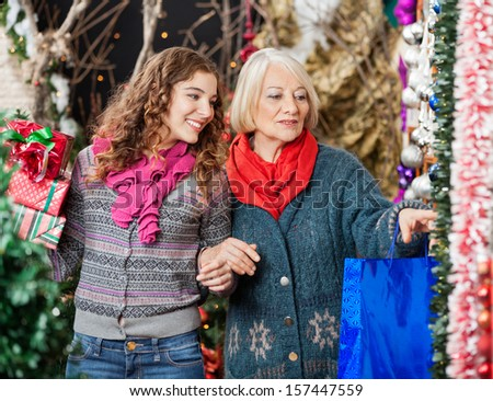 Happy mother and daughter shopping for Christmas ornaments in store - stock photo