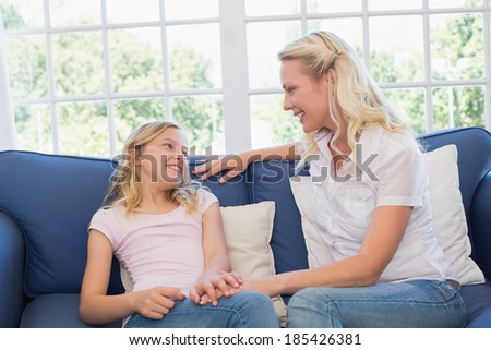 Happy mother and daughter sitting on sofa at home