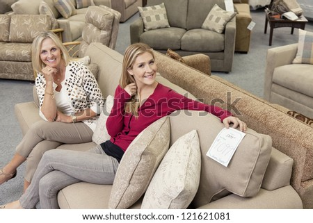 Happy mother and daughter sitting on sofa in furniture store - stock photo