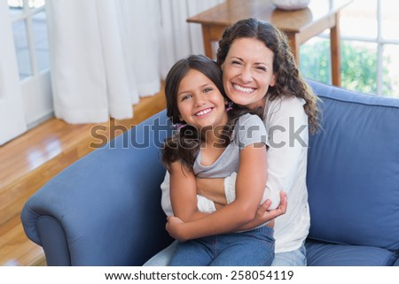 Happy mother and daughter sitting on the couch and smiling at camera in the living room - stock photo