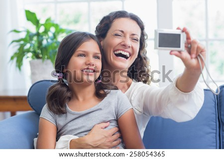 Happy mother and daughter sitting on the couch and taking selfie in the living room - stock photo