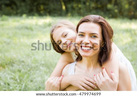 Happy mother and daughter smiling and hugging in a nature setting