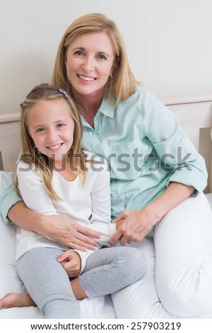 Happy mother and daughter smiling at camera in the bedroom