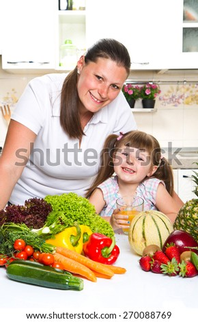 happy mother and daughter smiling in the kitchen
