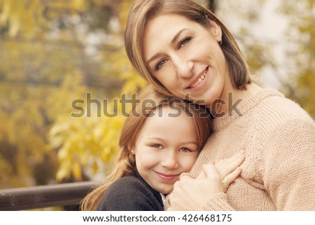 Happy mother and daughter smiling outdoors