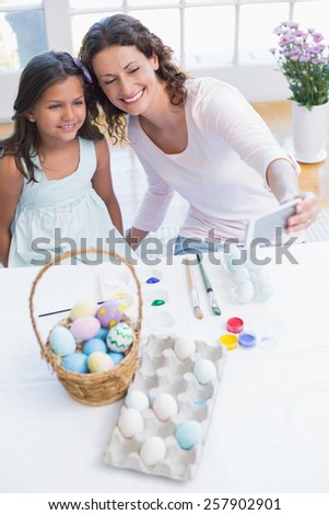 Happy mother and daughter taking selfie in the living room - stock photo