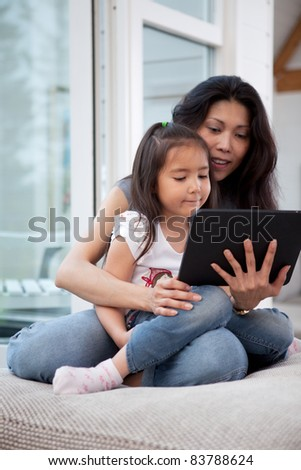 Happy mother and daughter using a digital tablet in a home interior, shallow depth of field with critical focus on child - stock photo