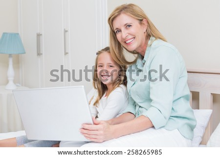 Happy mother and daughter using laptop in bed - stock photo