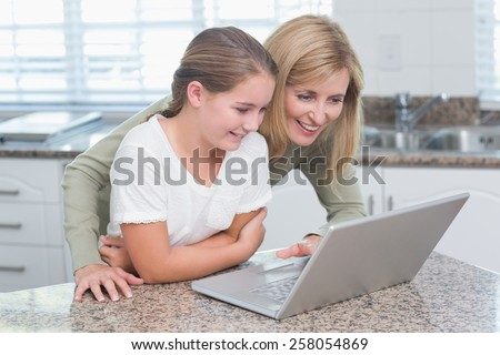 Happy mother and daughter using laptop together at home in the kitchen