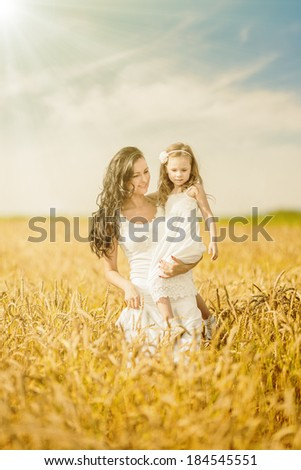 Happy mother and daughter walking among wheat ears beneath bright shining - stock photo