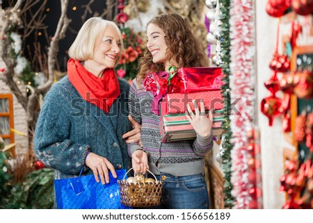 Happy mother and daughter with Christmas presents standing at store - stock photo