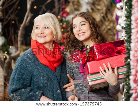 Happy mother and daughter with Christmas presents standing together at store