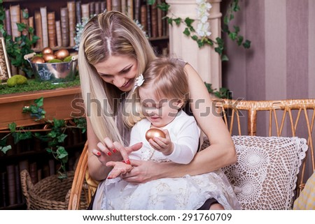 Happy mother and daughter with Easter golden egg - stock photo