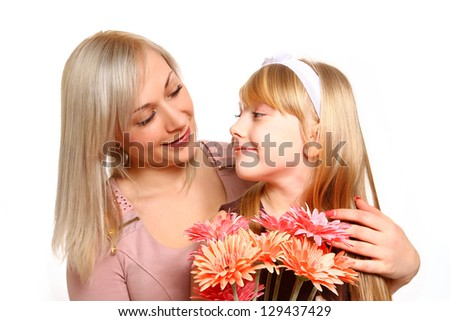 Happy mother and daughter with flowers looking at each other