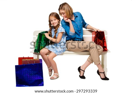 Happy mother and daughter with shopping bags sitting at studio, isolated on white background. they are considering purchasing and wonder - stock photo
