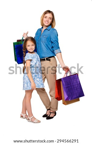 Happy  mother and daughter with shopping bags standing at studio, isolated on white background.   - stock photo