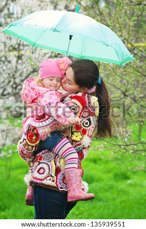Happy mother and daughter with umbrella - stock photo