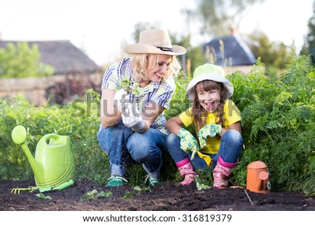 Happy mother and daughter working in the garden - stock photo