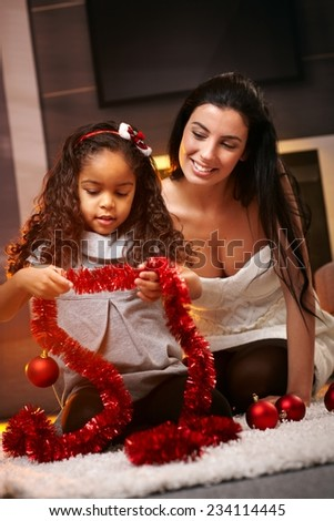 Happy mother and ethnic daughter at christmas time, smiling, playing with decorations. - stock photo