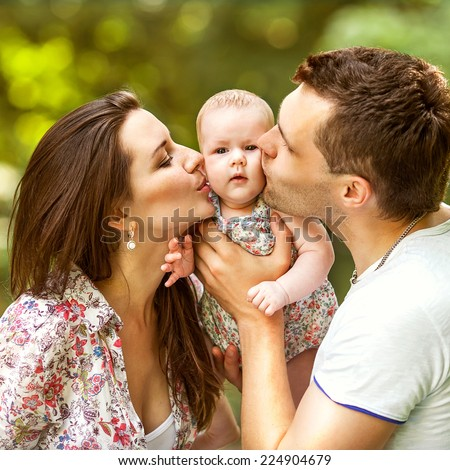happy mother and father kissing his little daughter  in park - stock photo