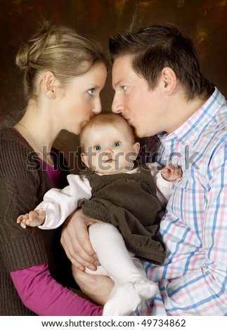 Happy mother and father kissing their 4 months old baby - stock photo